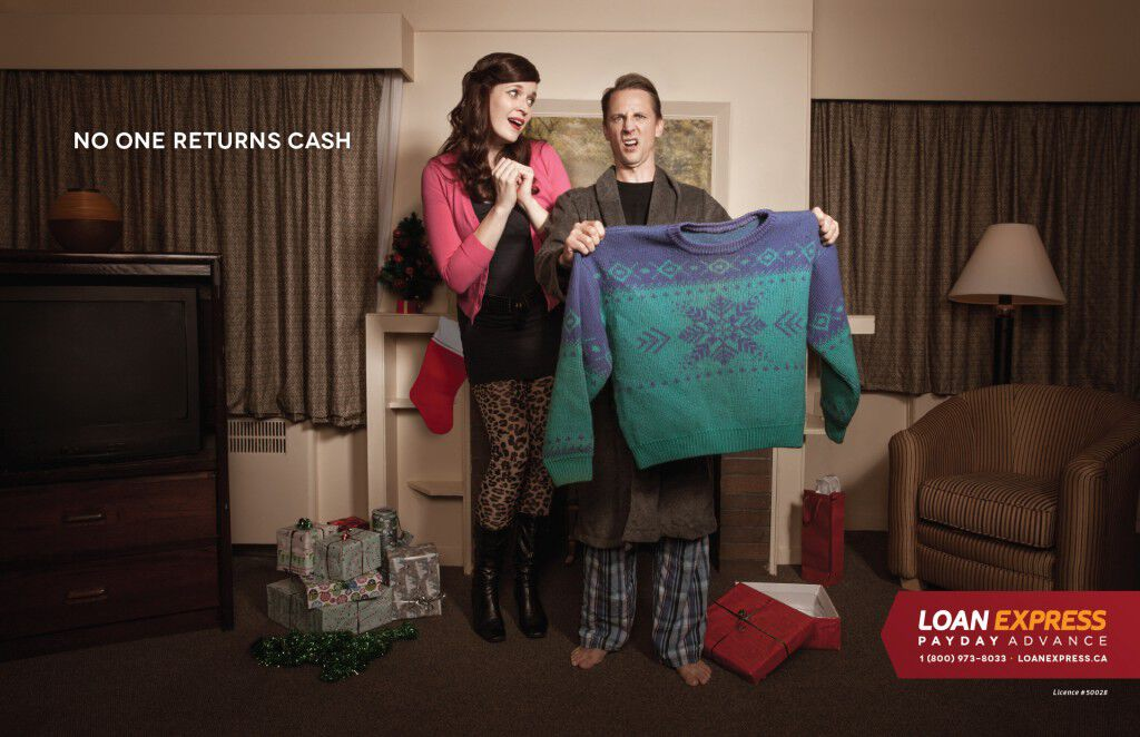 Loan Express Ad - no one re-gifts money. Shot of guy holding up extra large Christmas sweater